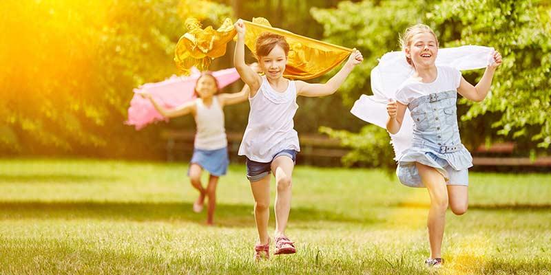 Glückliche Kinder rennen auf einer Wiese