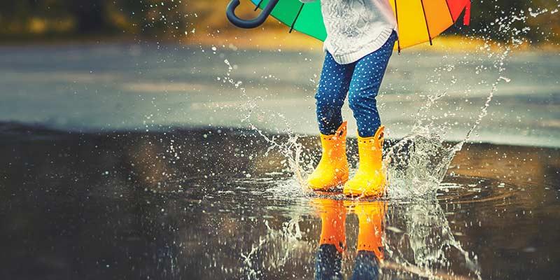 Kind hüpft mit Regenschirm in eine Pfütze