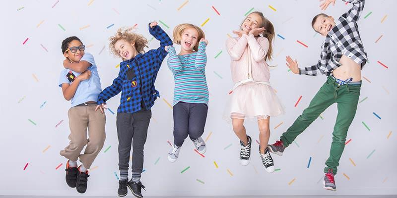 Eine fröhliche Gruppe von Kindern springt vor einer bunten Wand in die Luft